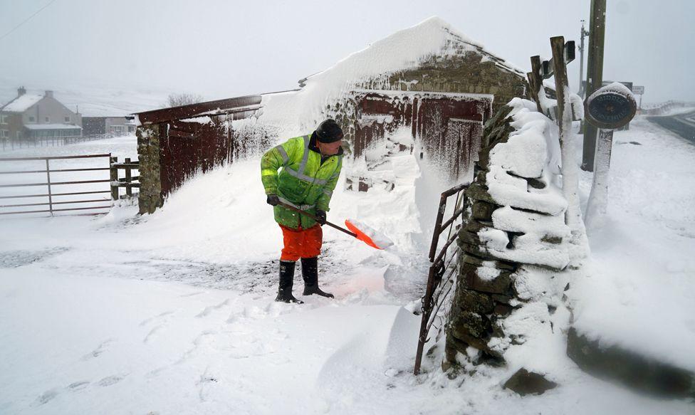 A man clears a snow drift in Lanehead, County Durham, 21 January 2021
