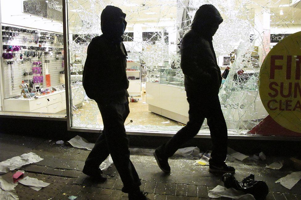 Two men with their faces covered walk past a looted shop during the riots in 2011