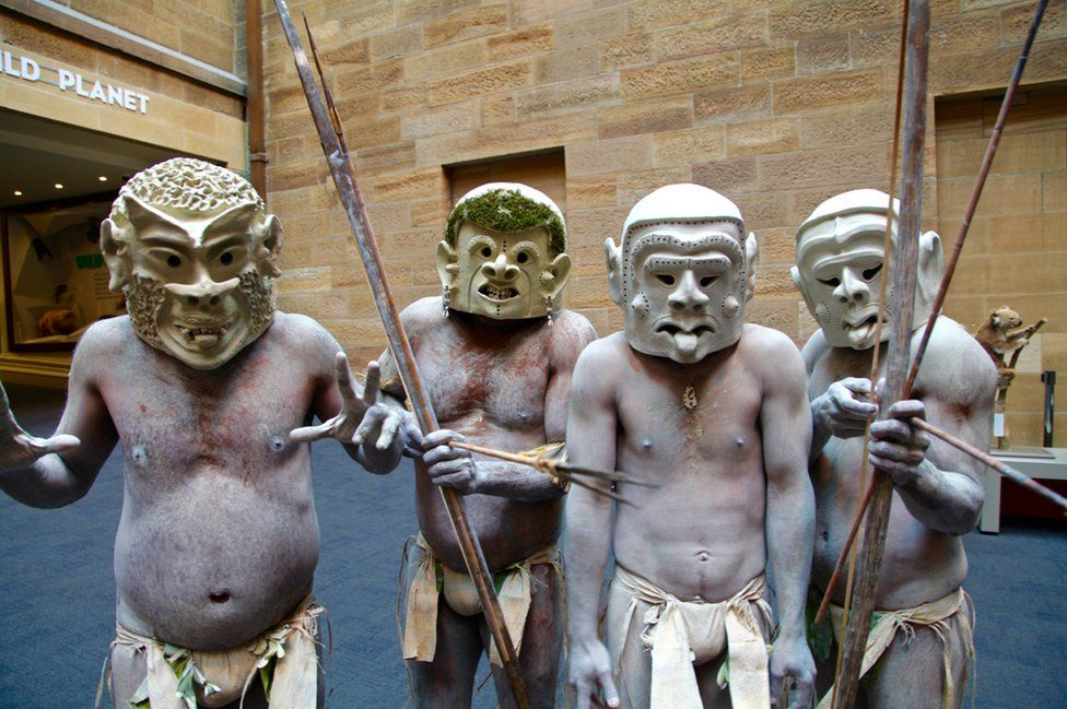 The four mud men who have travelled to Sydney - wearing their scary clay masks with painted white bodies and holding bows and arrows