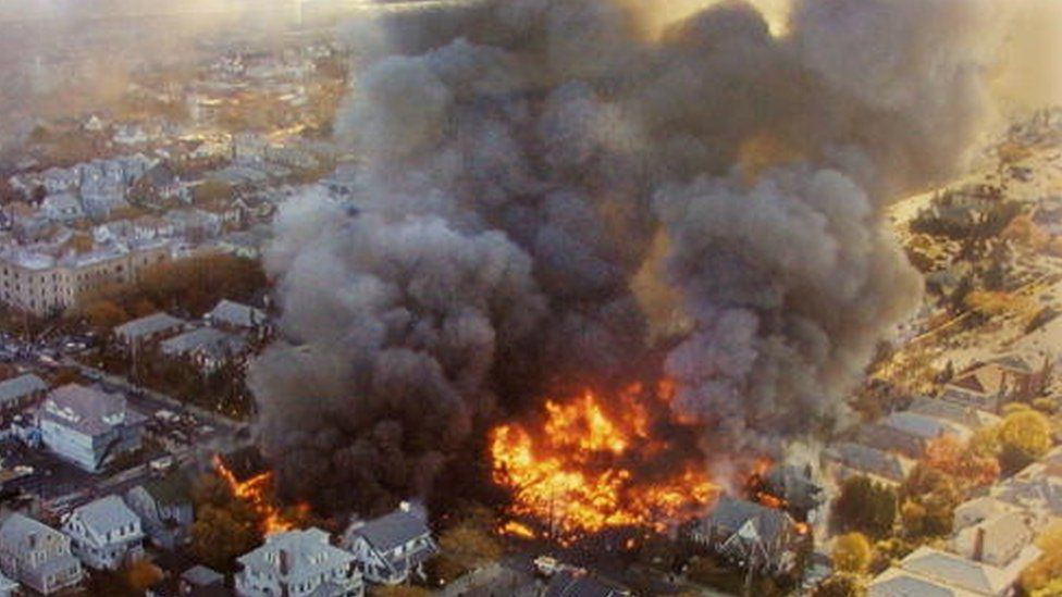 The wreckage of American Airlines flight 587 burns in the Rockaway neighbourhood of the Queens section of New York City (12 November 2001)