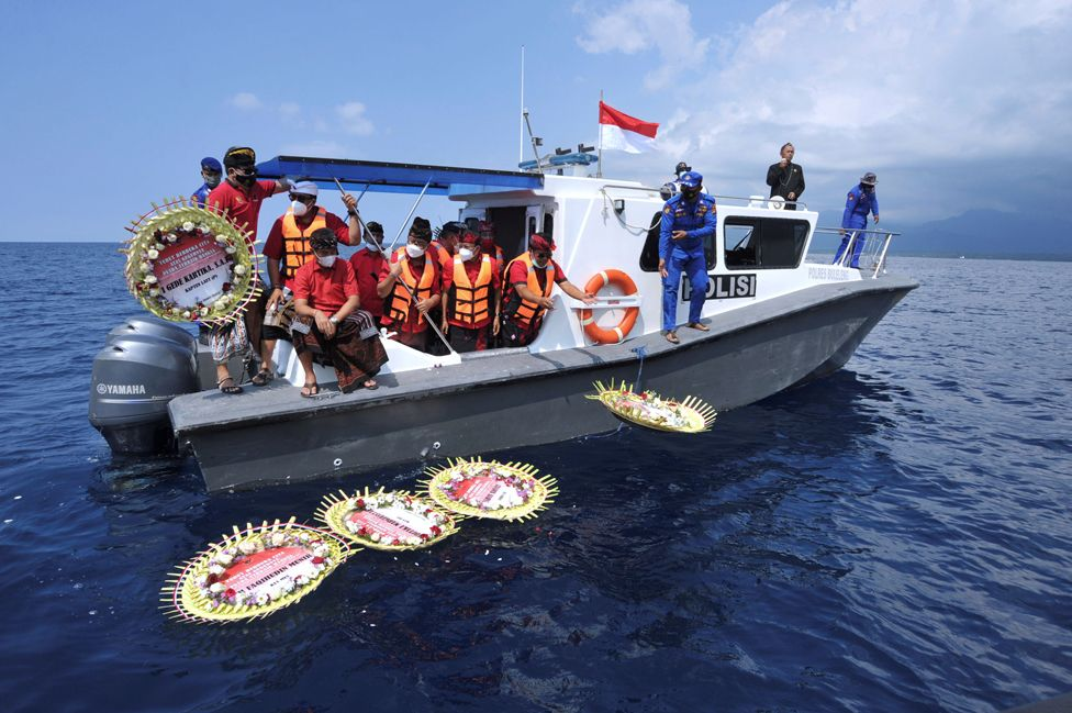 People on a boat throw flowers bearing the names of the sunken KRI Nanggala-402 submarine crew, near Labuhan Lalang, Bali, Indonesia, on 26 April 2021