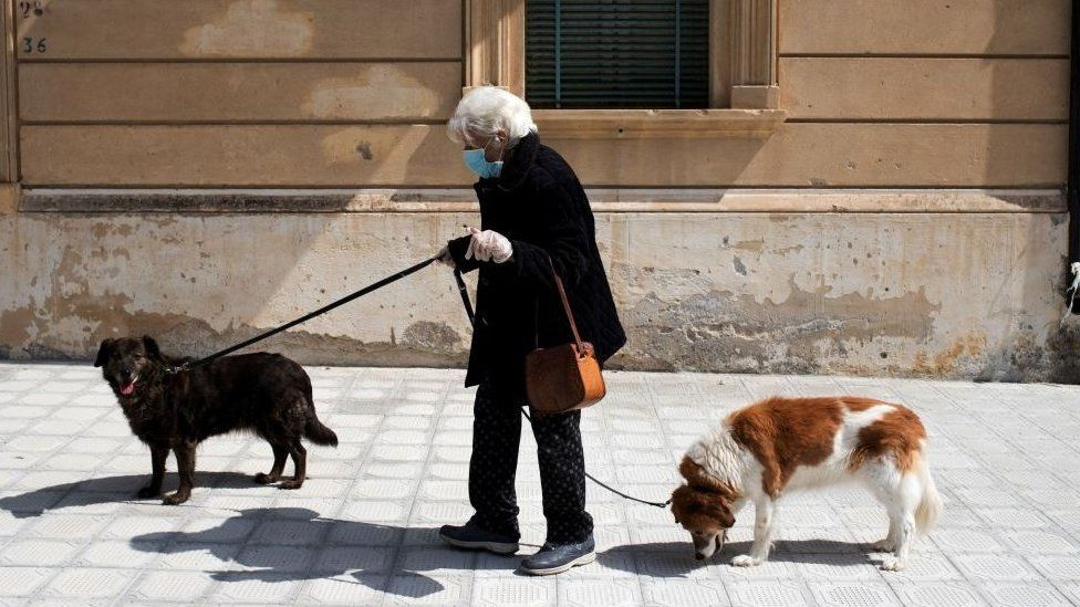 Woman walks her dogs in Locri, Calabria region, southern Italy - 8 April