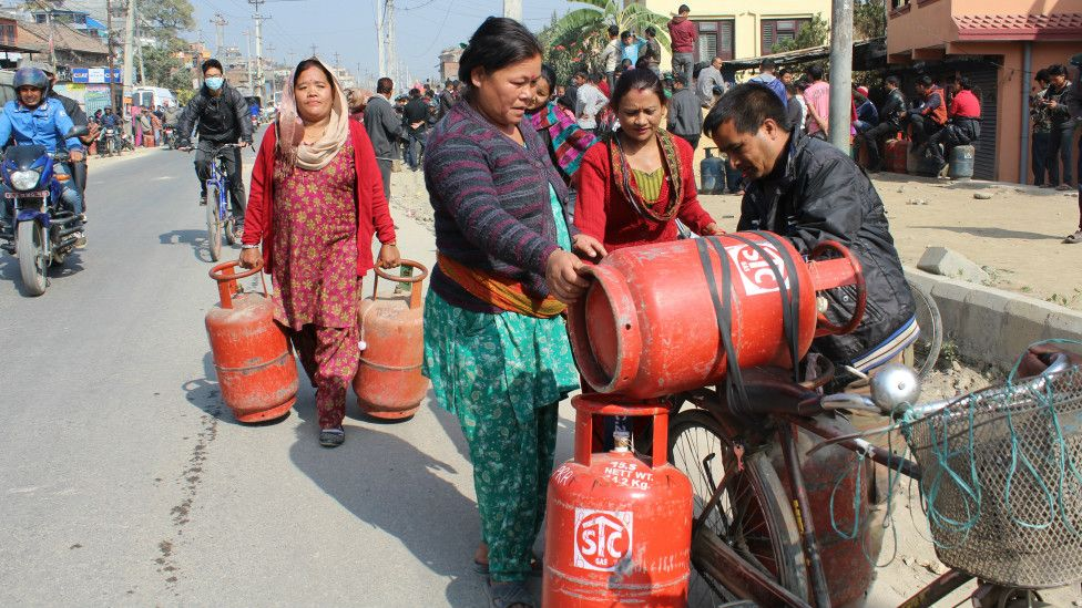 People carrying cooking gas in Nepal