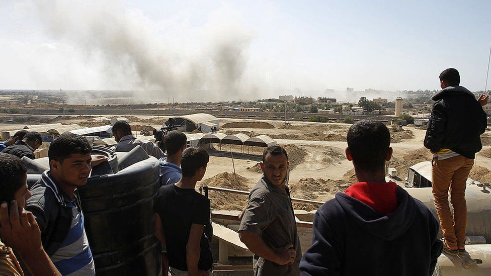 Palestinians watch smoke rising after Egypt destroys a tunnel on Egyptian side of the border