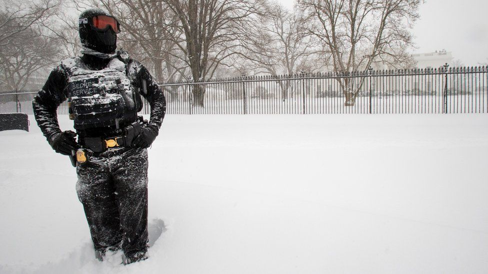 A uniformed U.S. Secret Service police officer stands guard in a knee-deep snow outside the White House in Washington, Saturday, Jan. 23, 2016