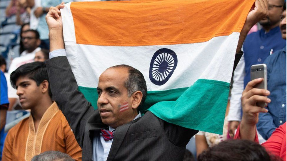 """A man holds up the flag of India as US President Donald Trump and Indian Prime Minister Narendra Modi attend """"Howdy, Modi!"""" at NRG Stadium in Houston, Texas, September 22, 2019"""