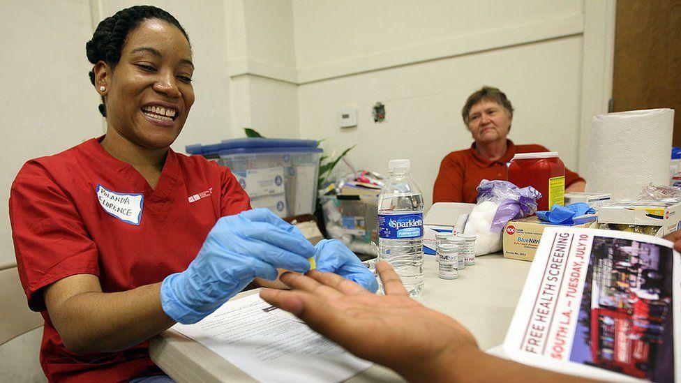 A UCLA nurse checks the gluclose level of a man during a health screening