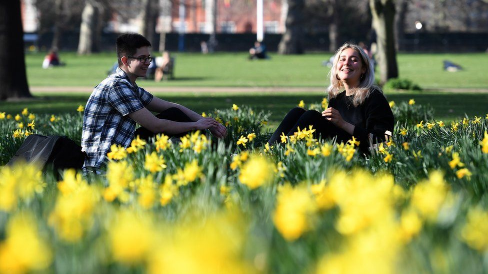 Two people sit among the daffodils in St. James's Park in London on Tuesday
