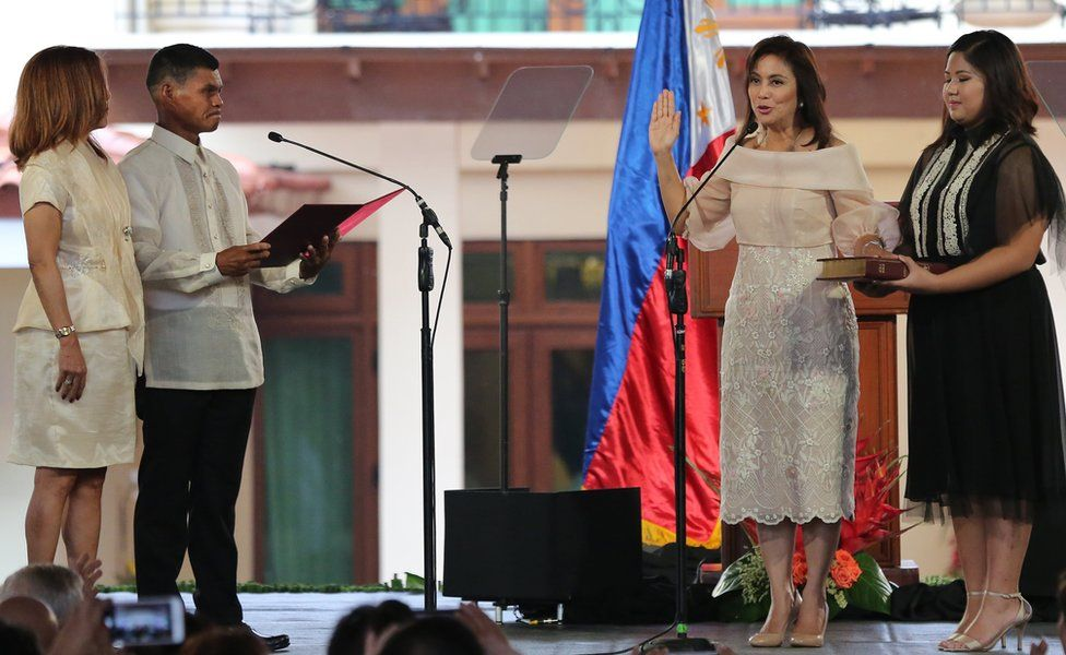 Philippine Vice President Leni Robredo, second right, is sworn in by village chiefs Ronaldo Coner and Regina Celeste during her inauguration ceremony in Quezon City, north of Manila on 30 June 2016.