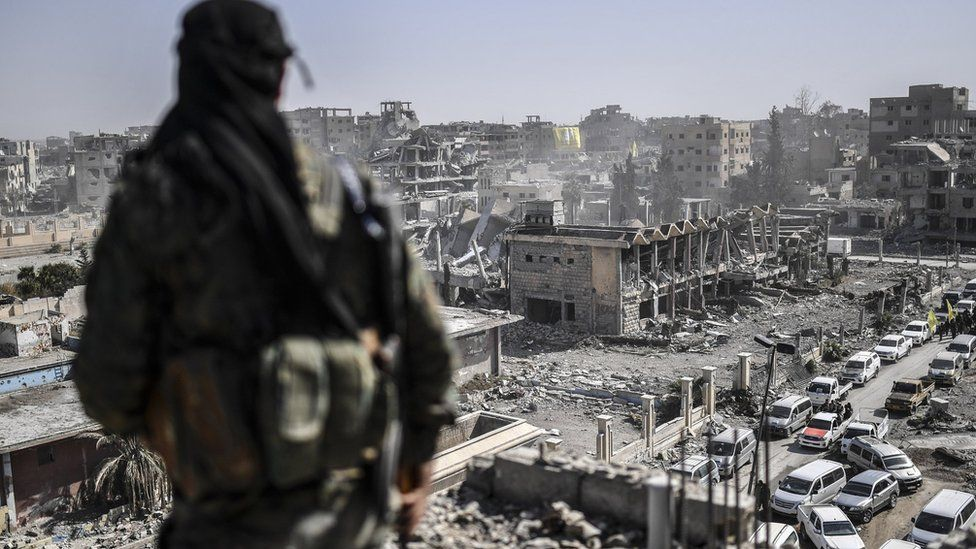 A fighter of the Syrian Democratic Forces stands guard on a rooftop in Raqqa after retaking the city from Islamic State