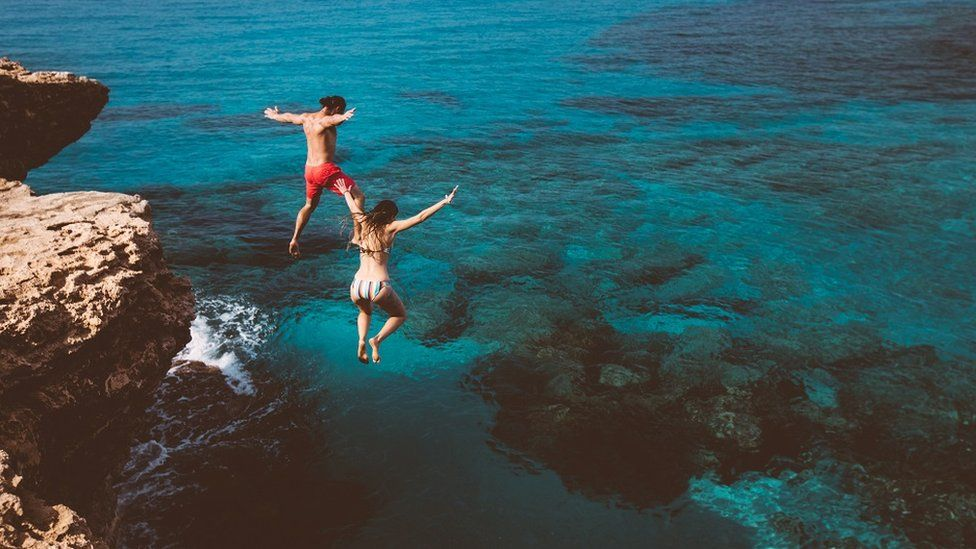 A couple jumping into beautiful blue water