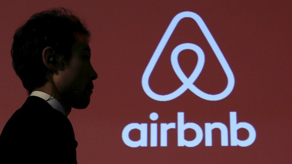 A man walks past a logo of Airbnb