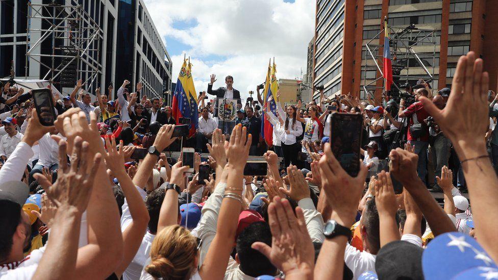 Citizens raise their hands as Juan Guaido, President of the Venezuelan Parliament, announces that he assumes executive powers