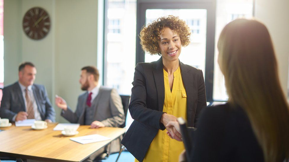 Women shaking hands in boardroom