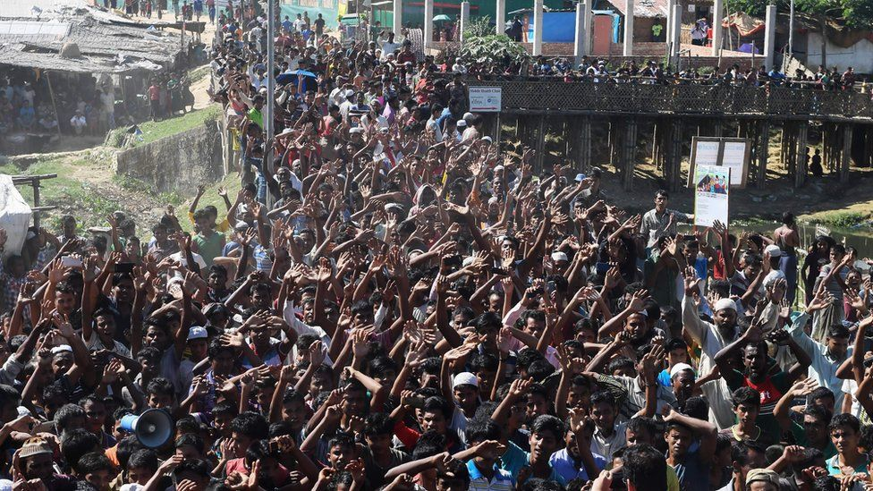 Hundreds of refugees protesting with their hands in the air
