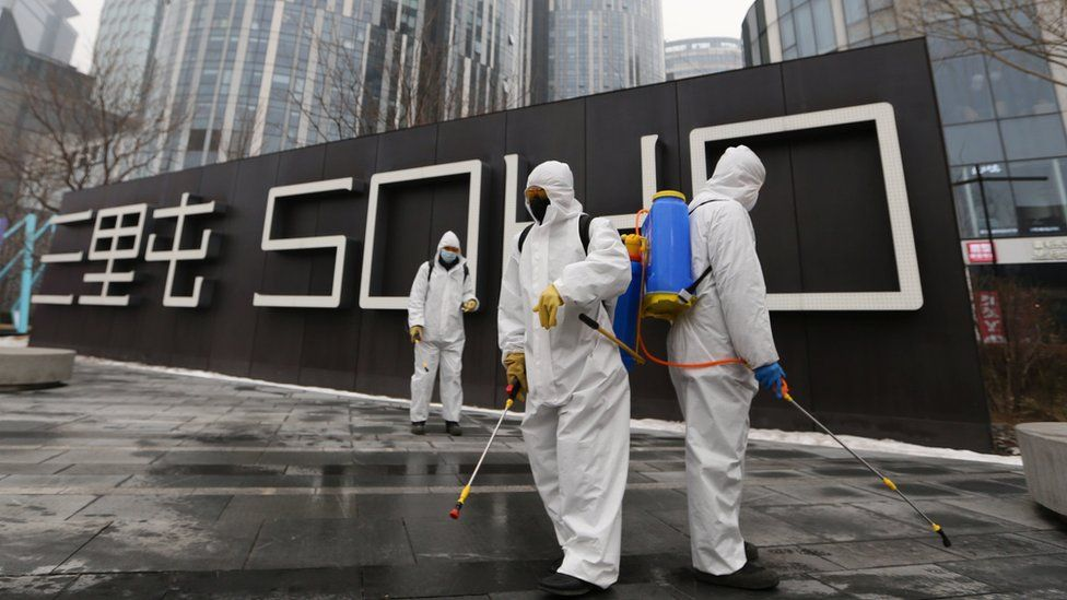 Workers wearing protective suits disinfect a commercial complex in Beijing following an outbreak of the coronavirus