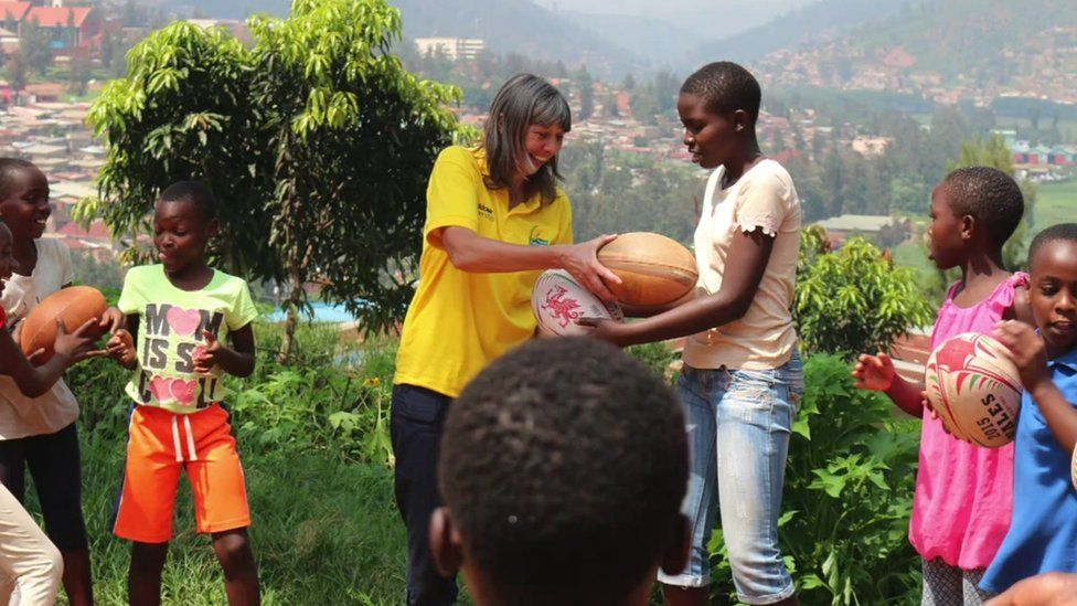 Mary Watkins giving out rugby kit to Rwandan children