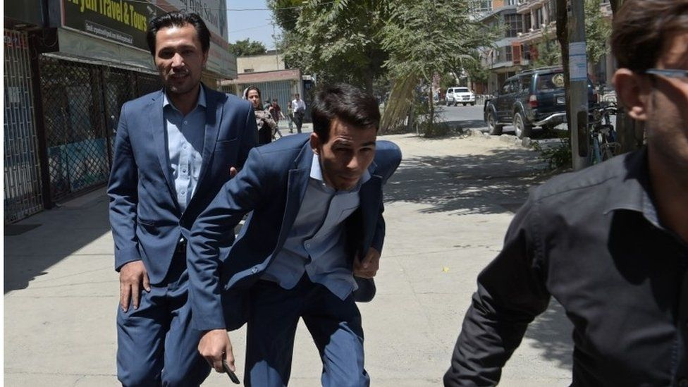 Afghan residents run at the site of a suicide blast near Iraq's embassy in Kabul on 31 July 2017