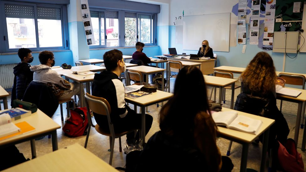 Students and a teacher sit in a classroom in Rome, wearing masks and socially distancing