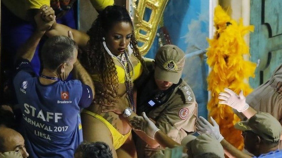 Firefighters and carnival staff carry a woman out of a float after an accident during the performing of the Unidos da Tijuca samba school for the Carnival celebrations at the Sambadrome in Rio de Janeiro, Brazil, Tuesday, Feb. 28, 201