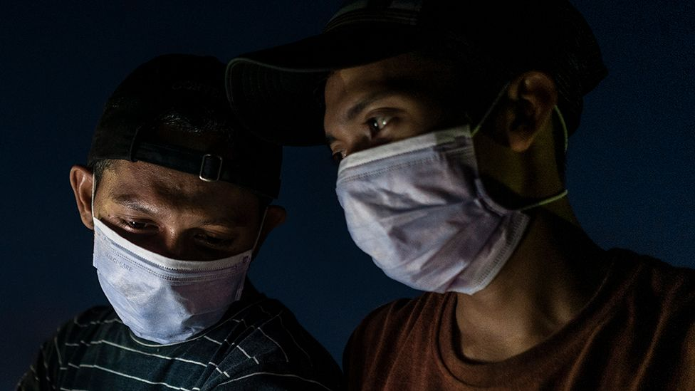 Two men wearing masks in Aceh