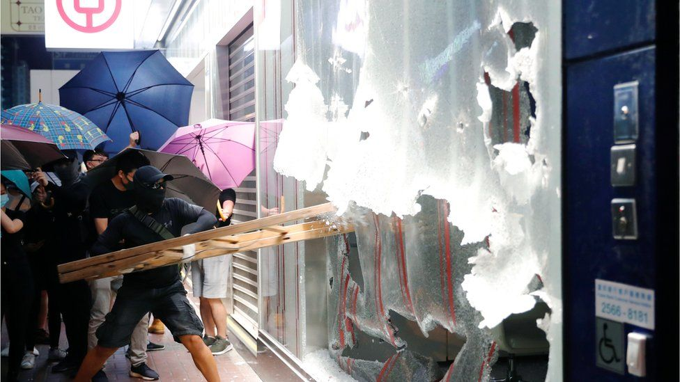 A man smashes the window of a Bank of China branch in Hong Kong with a ladder