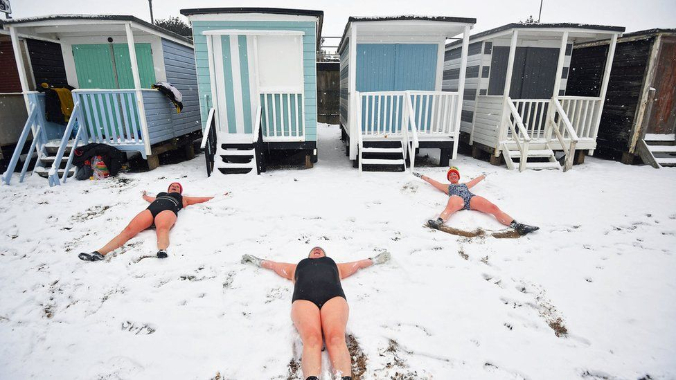 Swimmers makes angels in the snow at Thorpe Bay, Essex