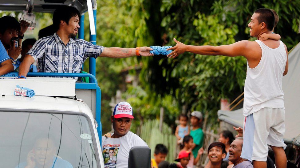 """Filipino boxing champion and senate candidate Emmanuel """"Manny"""" Pacquiao, riding on the top of an election vehicle, hands a rolled up blue election shirt to a villager holding a child during a political campaign in the town of Bay, Laguna province on 28 April 2016"""