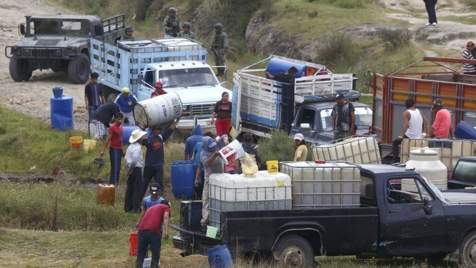 People fill large drums of fuel from a clandestine outlet c, in the state of Puebla, Mexico, 23 October 2017