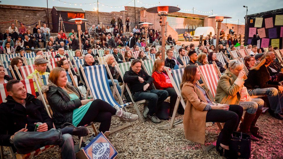 Crowds gather to watch an evening of comedy at Banksy's Dismaland theme park in Weston-super-Mare