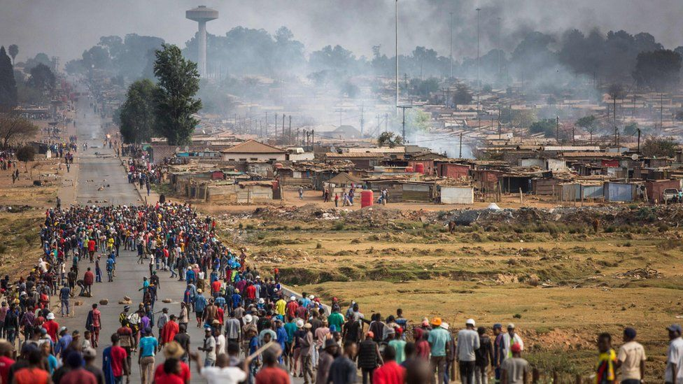 A mob armed with spears, batons and axes run through Johannesburg's Katlehong Township during a new wave of anti-foreigner violence on 5 September