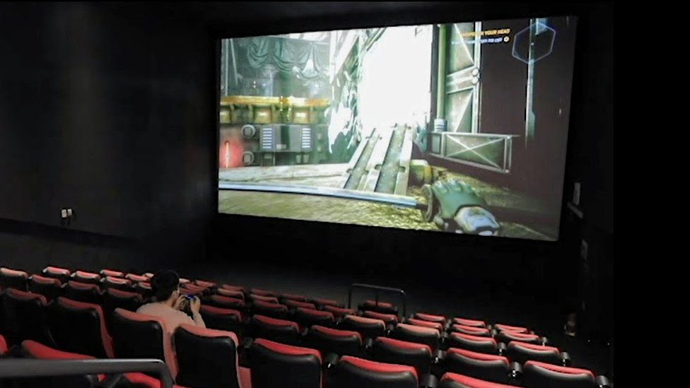 A young man playing computer games in a CGV cinema in South Korea