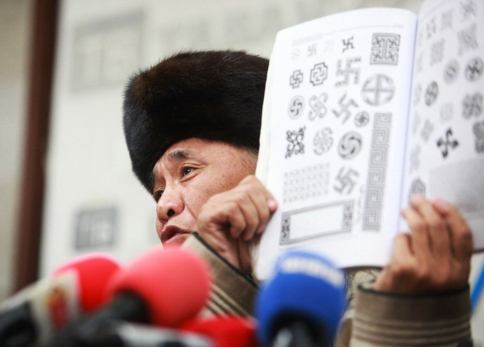 Sevjidiin Sukhbaatar, the father of injured Mongolian rapper Amarmandakh Sukhbaatar, displays a book showing traditional swastika patterns at a press conference about his son in Ulan Bator, Mongolia, on December 2, 2016.