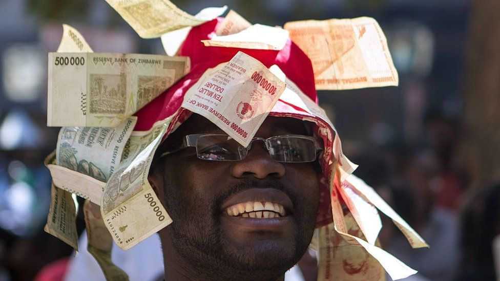 A man wearing a hat decorated with worthless note bearers' cheques during a protest against government plans to introduce bond notes