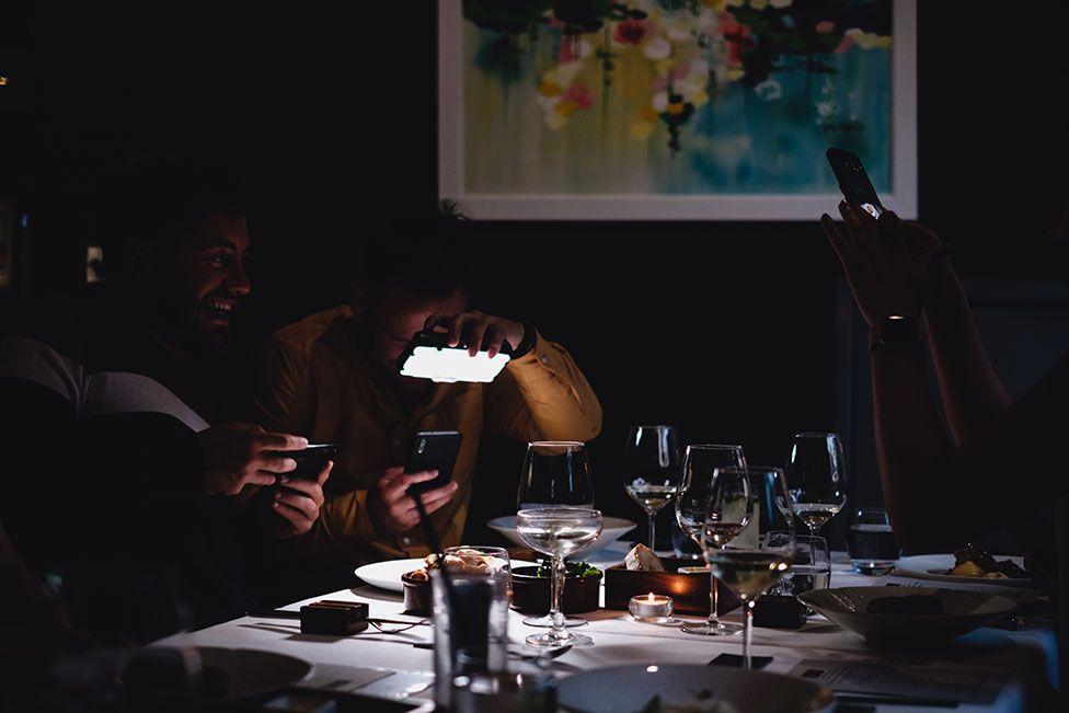 رجلان يلتقطان صور طعامهما في مطعم