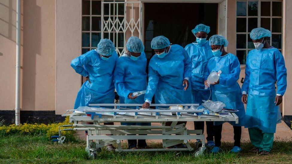 Medical personnel dressed in personal protective equipment are seen at a lodging building readying for their turn to go and work inside the main COVID-19 treatment center at Kamuzu Central Hospital in Lilongwe, Malawi, on January 18, 2021.
