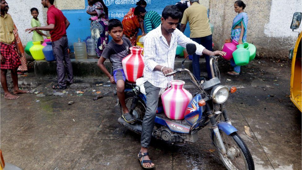 An Indian man with kid arranges plastic vessels filled with drinking water on his scooter at a water distribution point, which are replenished by water tankers, in Chennai, capital of the southern Indian state of Tamil Nadu, Wednesday, June 20, 2019.