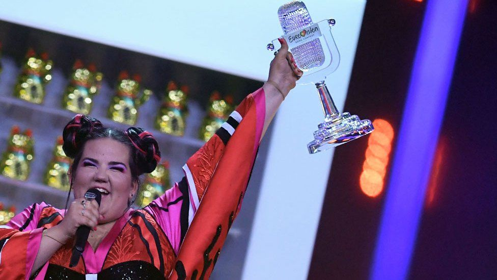 Netta holding the Eurovision trophy aloft