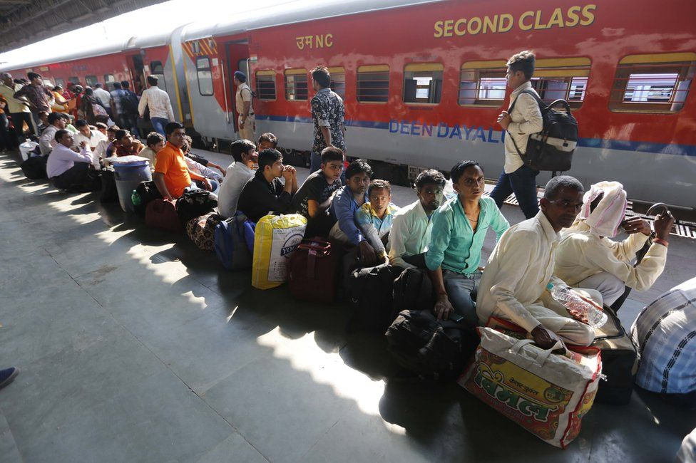 Migrants from the states of Uttar Pradesh and Bihar wait in queue to board a train to return home following attacks on migrants.