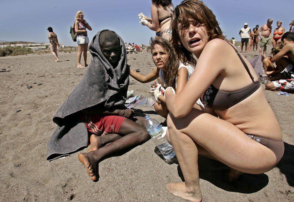 Tourists help a migrant boy on La Tejita beach, Tenerife