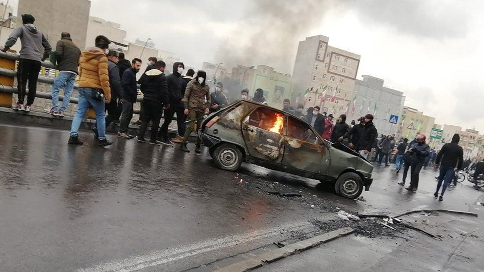Protesters stand around a car that has been set on fire in Tehran