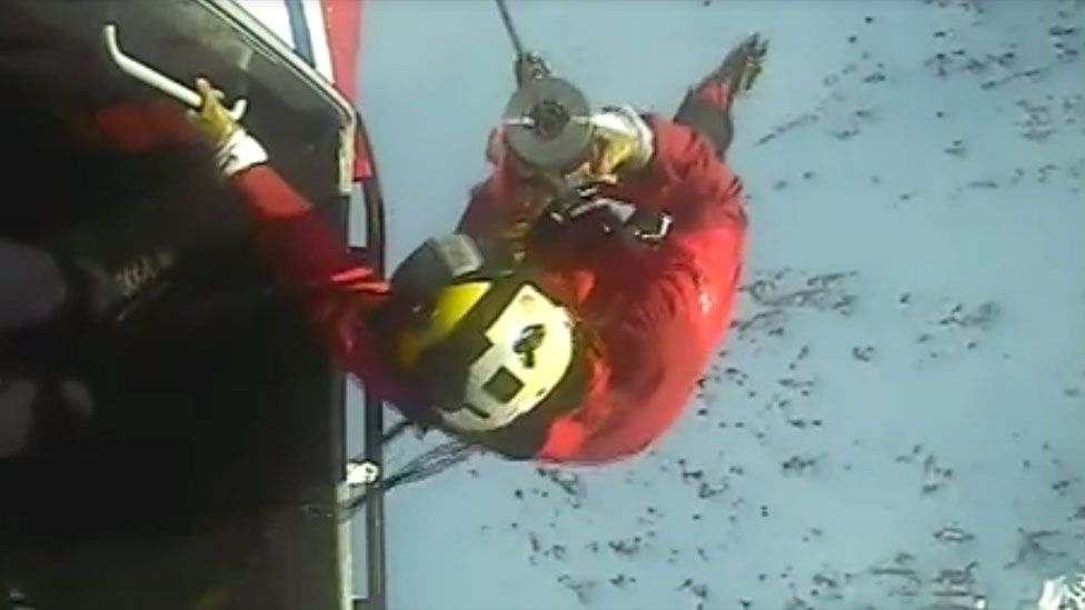 Paramedic winchman begins descent to the casualty