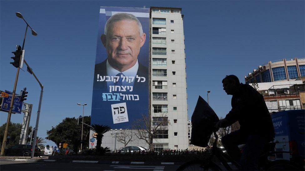 A man passes a Blue and White billboard in Tel Aviv showing Benny Gantz (9 April 2019)