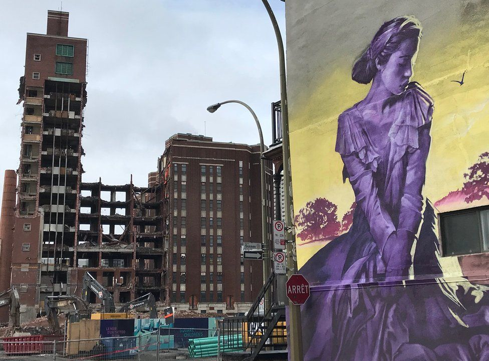 A building is demolished in the background with a street art in the foreground