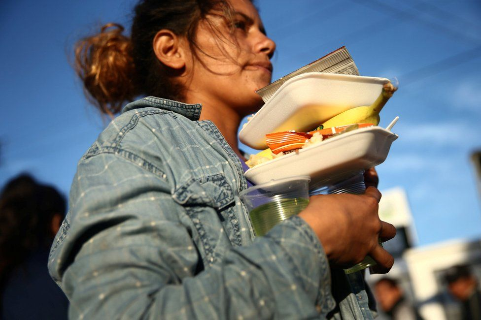 A migrant carries her food outside a temporary shelter in Tijuana, Mexico, 23 November
