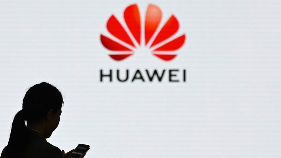 A woman in front of the Huawei logo