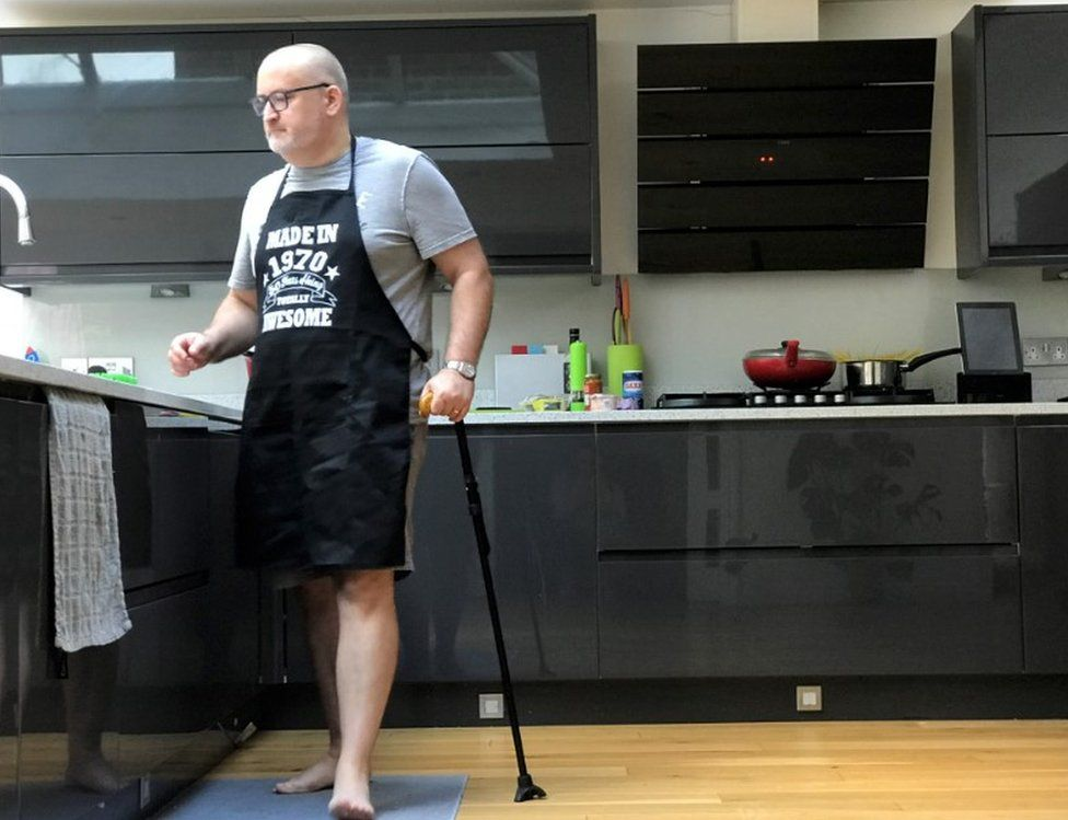 Ian Taverner standing in his kitchen with his walking stick