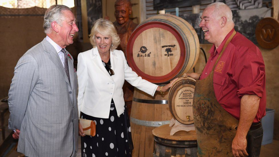 Prince Charles and the Duchess of Cornwall speak with a worker during a visit to Seppeltsfield Winery in the Barossa Valley, Australia
