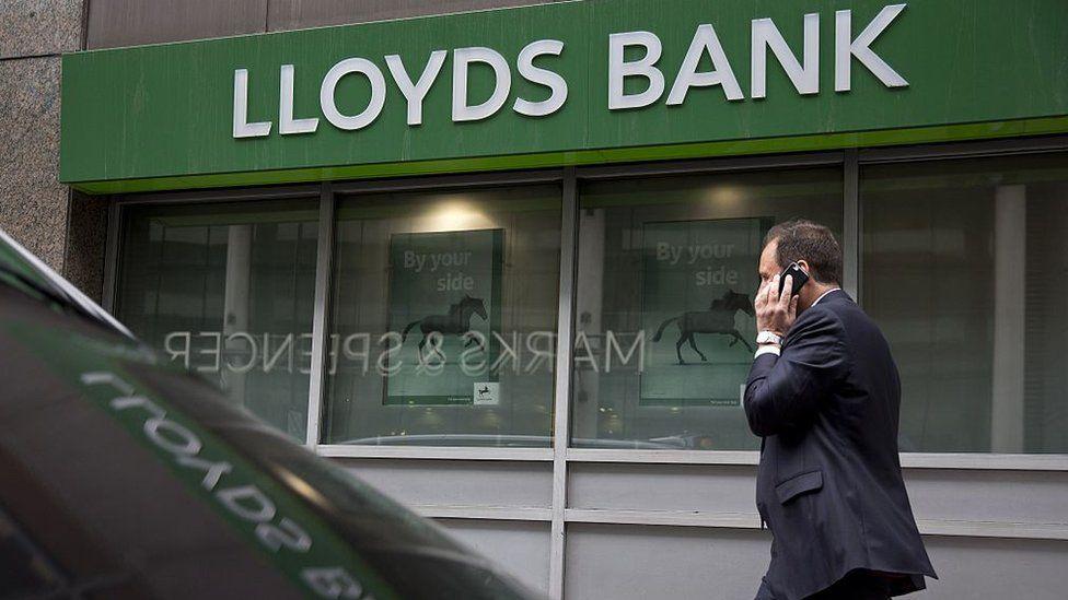 Man on phones walks past Lloyds Bank branch