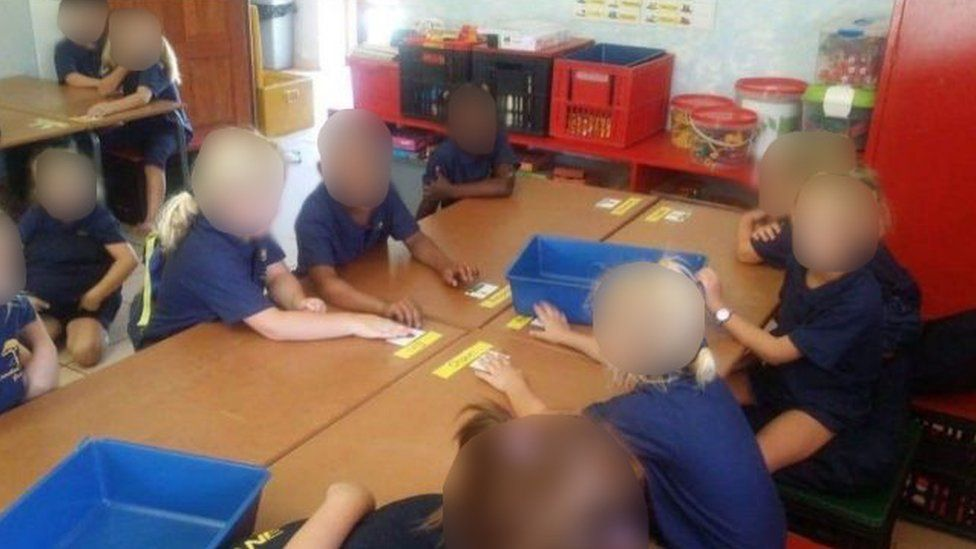 Black and white children sit together in mixed groups in South Africa